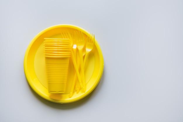 Utensilios de picnic de un solo uso amarillo sobre gris. espacio para texto.