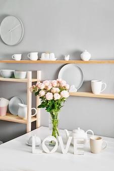 Utensilios, ramo de rosas y tazas en estante. platos en el armario de la cocina.