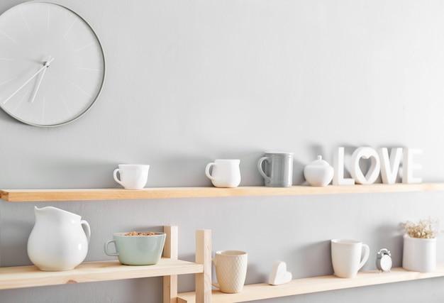 Utensilios y tazas en estante. platos en el armario de la cocina.