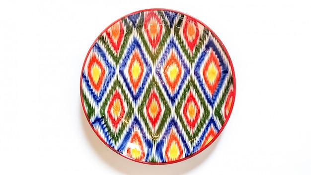Utensilios tradicionales uzbekos - plato con adorno ikat en blanco, aislado