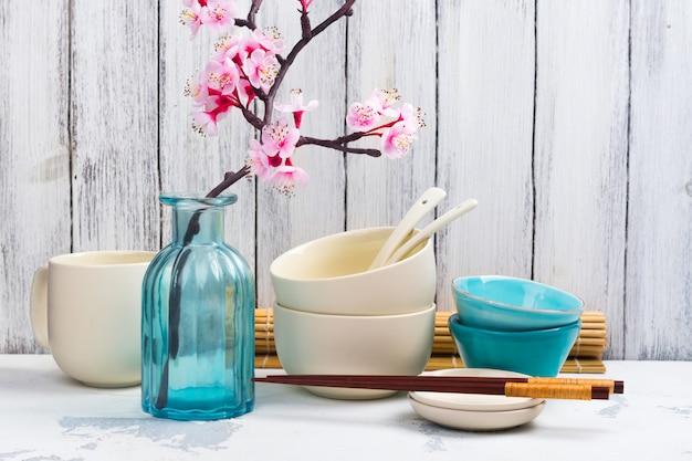 Utensilios, vajilla, palillos y rama japoneses de sakura floreciente en el fondo asiático blanco