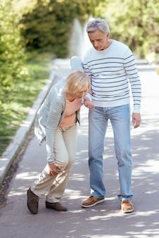 Útil hombre tranquilo jubilado que se preocupa por su anciana esposa y la ayuda a dar pasos mientras camina al aire libre