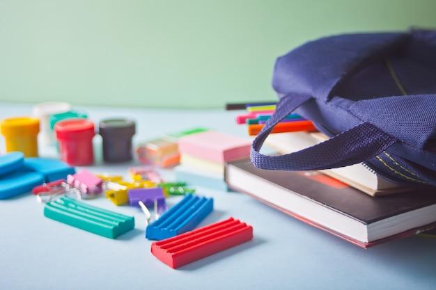 Útiles escolares y bolsa escolar en la mesa azul