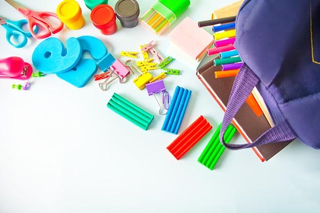 Útiles escolares y bolsa escolar sobre la mesa azul. copie el espacio.