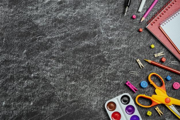 Útiles escolares de color en la pizarra