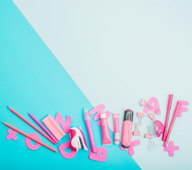 Útiles escolares de color rosa y alfabetos sobre fondo de doble color