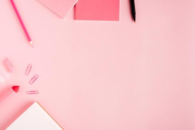 Útiles escolares de color rosa en el escritorio