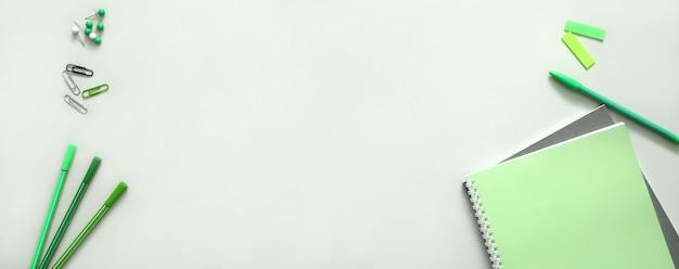 Útiles escolares en color verde. fondo de banner de regreso a la escuela para diseño web.