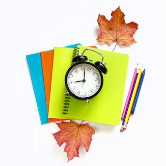 Útiles escolares de colores, cuadernos y reloj despertador en blanco.