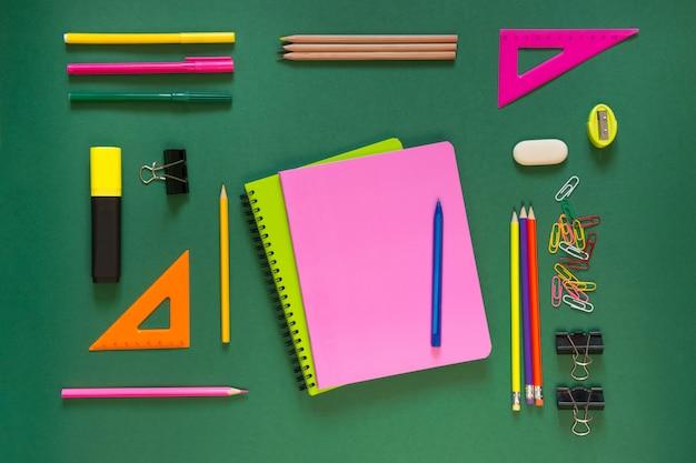 Útiles escolares de colores, libro rosa en verde.