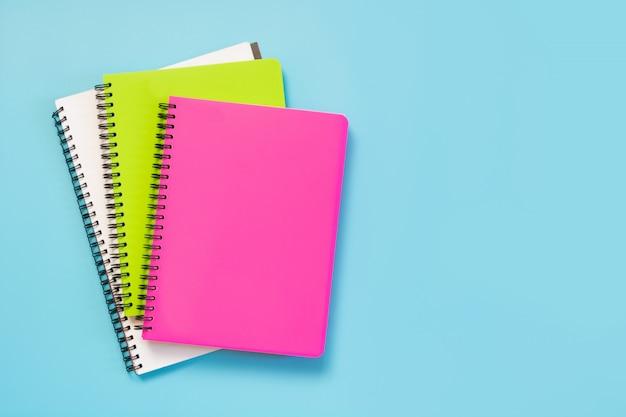 Útiles escolares de colores para niñas, cuadernos y bolígrafos en azul intenso. vista superior, aplanada. copia espacio