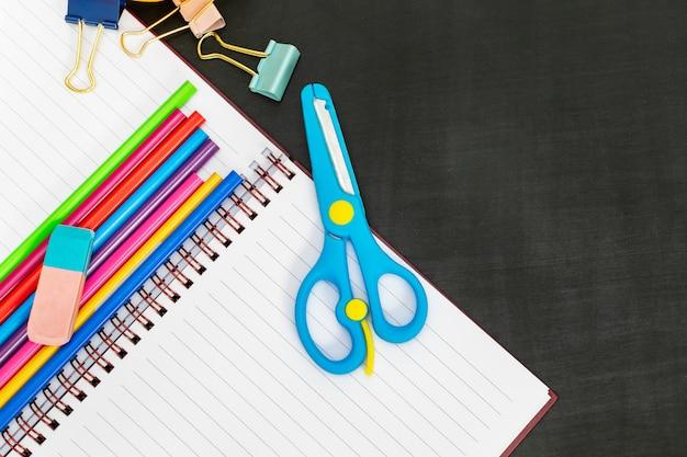 Útiles escolares con cuaderno, tijeras, sujetapapeles, lápices de colores.