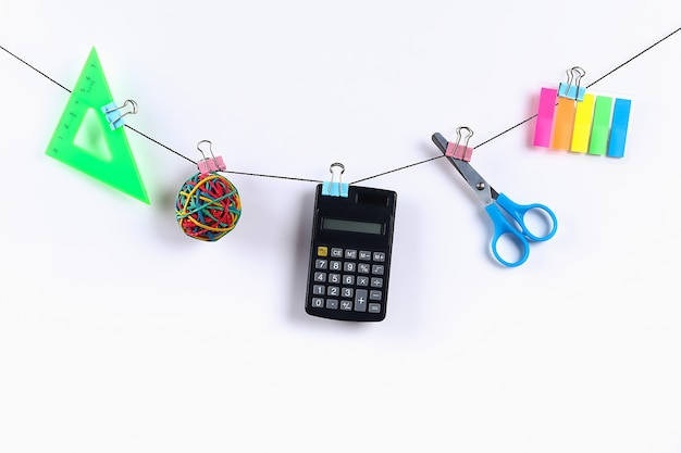 Los útiles escolares cuelgan de la cuerda. útiles escolares en blanco. concepto de regreso a la escuela