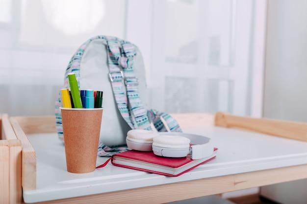 Útiles escolares en el escritorio de la escuela. mochila azul, auriculares blancos, cuaderno y bolígrafos en el frasco yacían sobre el pupitre blanco.