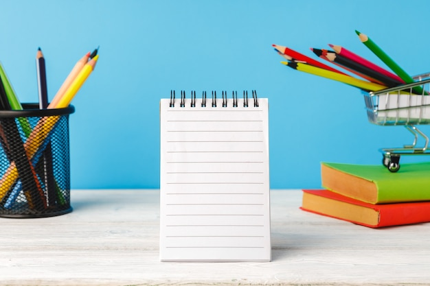 Útiles escolares en un escritorio de madera contra el fondo azul, vista frontal
