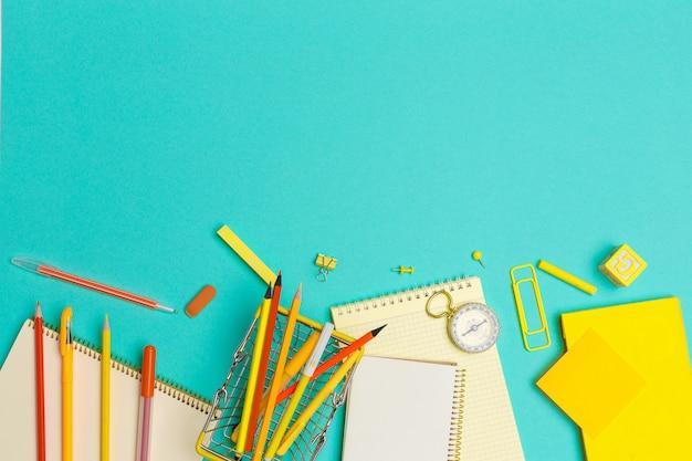 Útiles escolares en el fondo de papel colorido