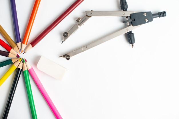 Útiles escolares y lápices de colores sobre blanco
