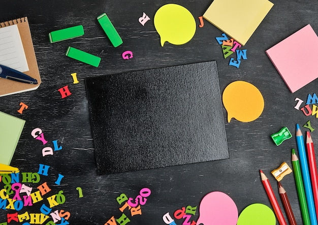 Útiles escolares: lápices de madera multicolores, cuaderno, pegatinas de papel, clips de papel, sacapuntas