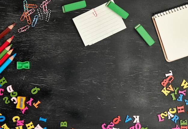 Útiles escolares, lápices de madera multicolores, cuaderno, pegatinas de papel, clips de papel.