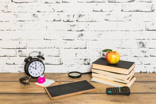 Útiles escolares y libros con manzana en la parte superior