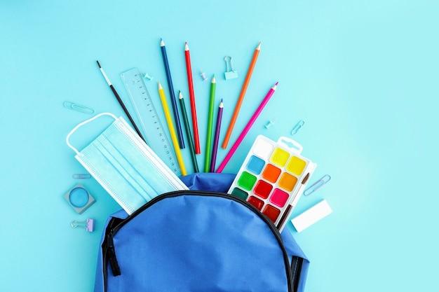 Útiles escolares y una máscara médica protectora vertida