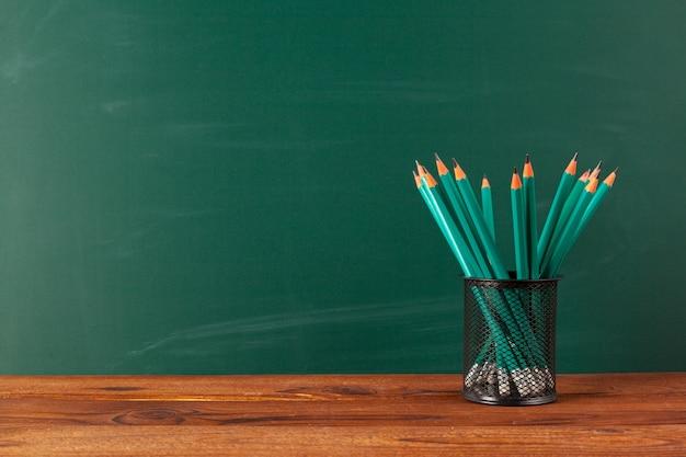 Útiles escolares en una mesa de madera y fondo de pizarra con copyspace
