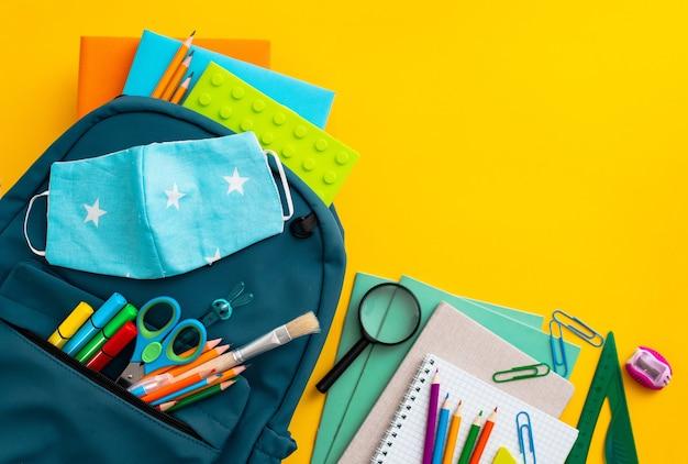 Útiles escolares mochila azul máscara médica fondo amarillo regreso a la escuela pandemia coronavirus con ...