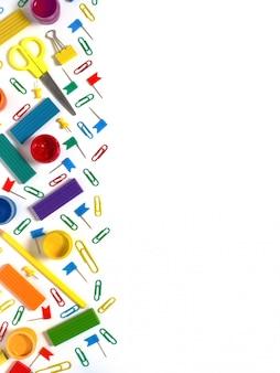 Útiles escolares multicolores en mesa blanca