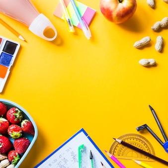 Útiles escolares del niño y almuerzo en cajas plásticas sobre fondo amarillo.