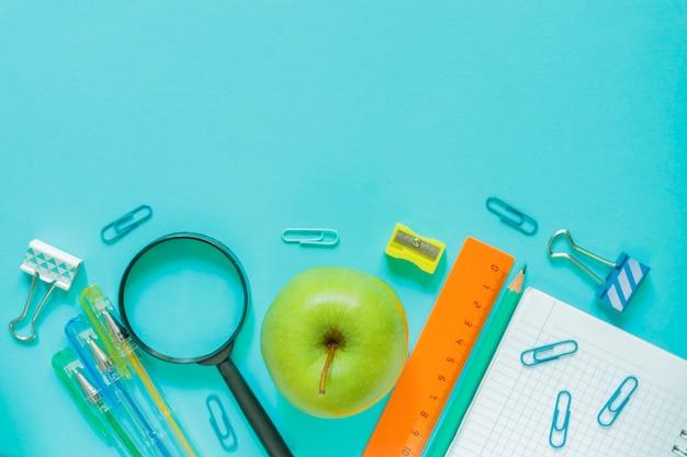 Útiles escolares de oficina sobre fondo azul