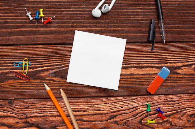 Útiles escolares con papel en blanco sobre mesa de madera