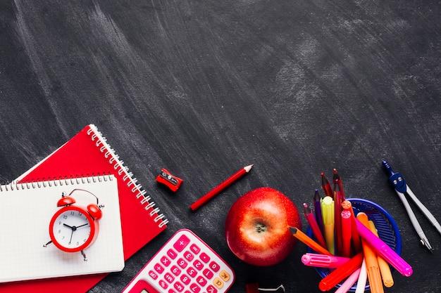 Útiles escolares rojo brillante y manzana en pizarra