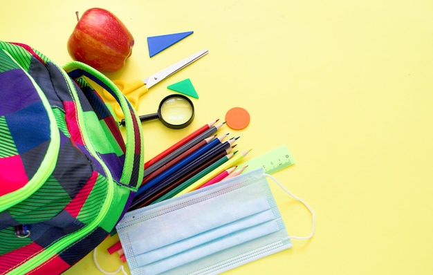 Útiles escolares sobre fondo amarillo. volver al concepto de escuela.