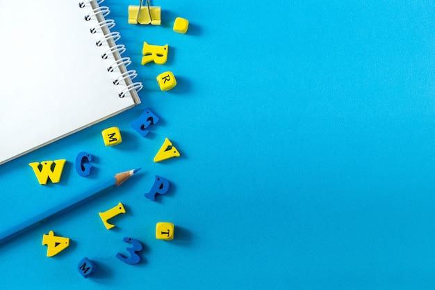 Útiles escolares sobre un fondo azul. concepto de día escolar y maestro. letras de madera sobre la mesa con espacio de copia.