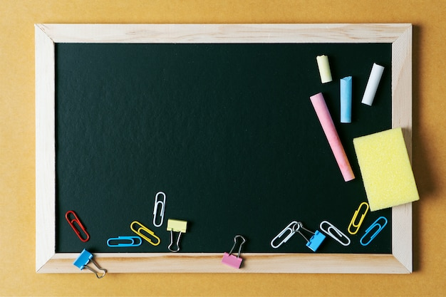 Útiles escolares sobre fondo de tablero negro. volver al concepto de escuela.