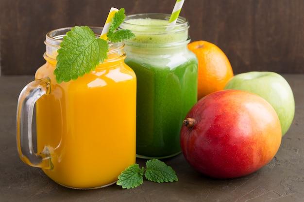 Útiles jugos de frutas y verduras. en el fondo oscuro