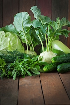 Útiles vegetales verdes en una mesa de madera