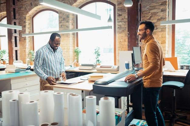 Utilizando tecnología moderna. dos hombres experimentados y trabajadores que utilizan tecnología moderna mientras trabajan en la impresión de libros