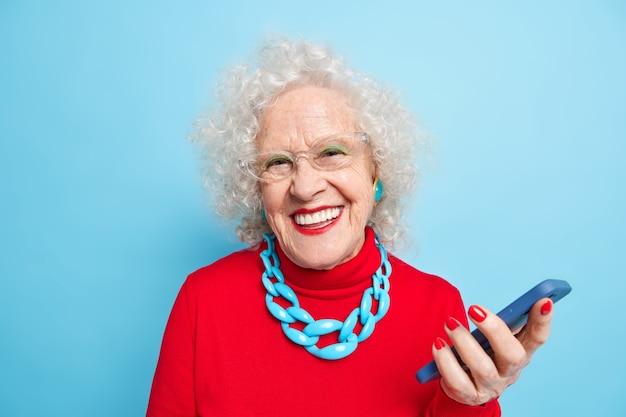 Utilizando tecnologías modernas entre todas las edades. madura mujer de pelo gris positiva con maquillaje brillante vestida con un jersey rojo con collar utiliza smartphone espera para llamar sonríe positivamente.