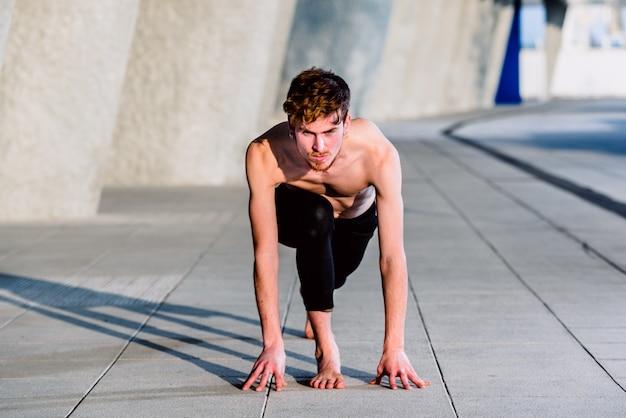 Utthita ashwa sanchalanasana, la postura del corredor en yoga, es útil para muchos deportes, el joven lo practica al aire libre.