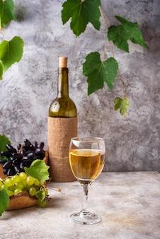 Uva, botella y copa de vino blanco.