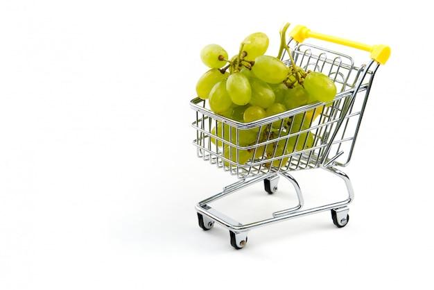 Una uva en carrito aislado sobre fondo blanco. maduras sabrosas uvas verdes en carrito de compras. concepto de comercio de uva. concepto de compra en línea. carro y uva sobre un fondo blanco.