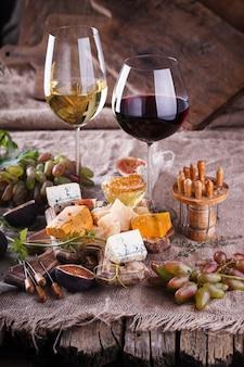 Uva, queso, higos y miel con un vaso de vino tinto y blanco.