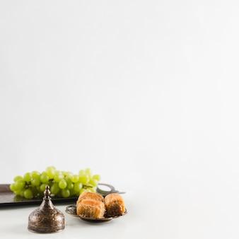 Uva verde en bandeja cerca de baklava