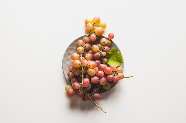Uvas aisladas. uva roja en un recipiente aislado sobre fondo blanco.