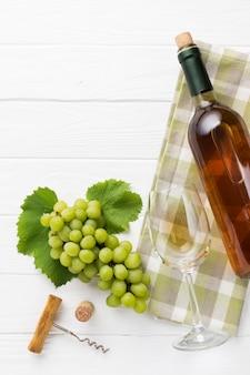 Uvas blancas y botella llena de vino.