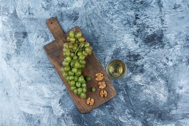 Uvas blancas laicas planas, nueces en tabla de cortar con copa de vino sobre fondo de mármol azul oscuro. horizontal