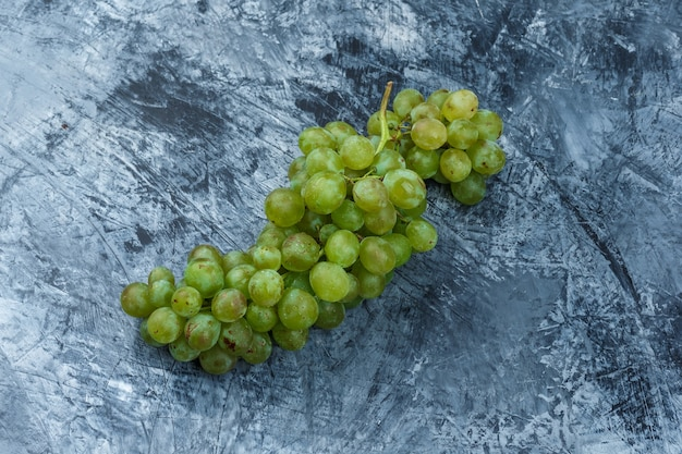 Uvas blancas laicas planas sobre fondo de mármol azul oscuro. horizontal