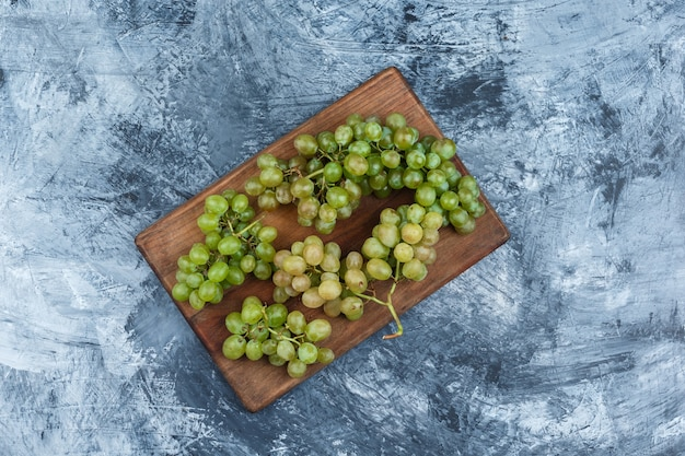 Uvas blancas laicas planas sobre tabla de cortar sobre fondo de mármol azul oscuro. horizontal