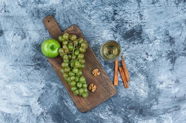 Uvas blancas, nueces, manzana sobre una tabla de cortar con un vaso de whisky, vista superior de canela sobre un fondo de mármol azul oscuro